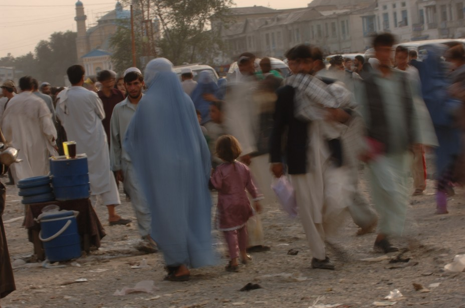 A woman in a burqa holds a small girls hand and moves through a crowded street
