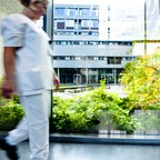 A worker walks through a glass-enclosed hallway facing a courtyard at St. Olav's Hospital in Trondheim, Norway.