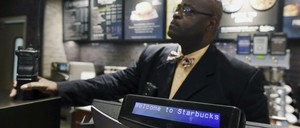 A plain-clothed police officer mans a position behind the counter at the Starbucks that has become the center of protests in Philadelphia.