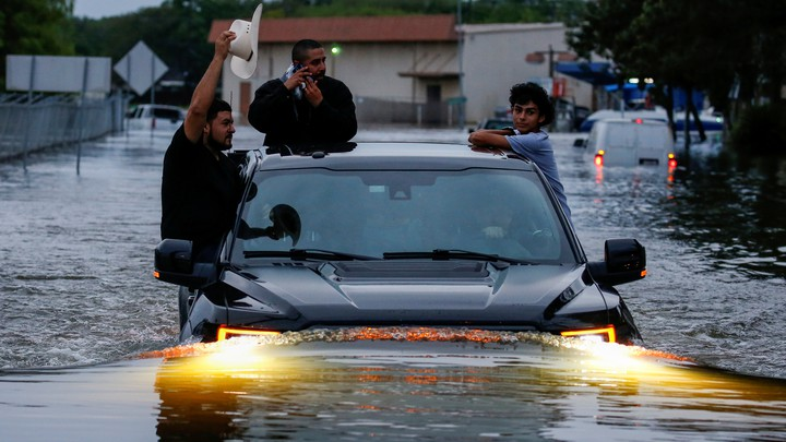 Three people hang onto the outside of a truck as it travels through floodwaters in Houston.
