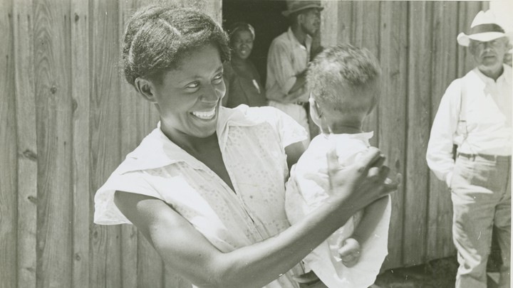 A woman holds a child.