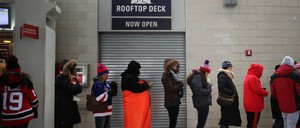 Women wait in a long line for the public bathroom at a sports arena.