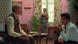 """Three men, writers and editors of """"The French Dispatch,"""" in a pink room that features a large window, bold, floral-patterned drapes, and plants"""