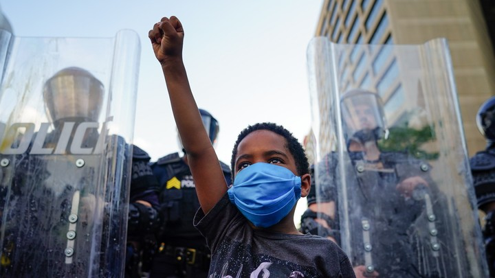 A young black boy wearing a mask raises his fist in front of a line of police officers using riot shields