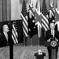 The U.S. president stands alongside the leaders of Australia and Britain on video screens.