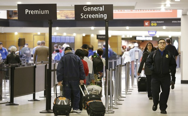 "Travelers at an airport stand in lines marked ""Premium"" and ""General Screening."""