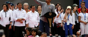 Indonesia's President Joko Widodo speaks at a podium as people photograph him.