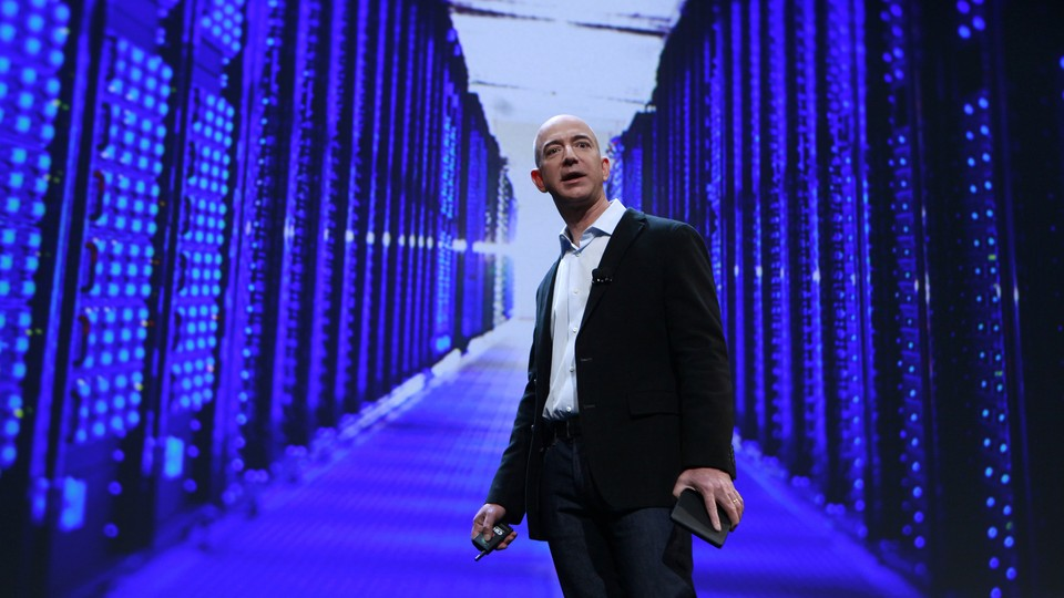 Jeff Bezos stands in front of a purple, blue, and black data center.