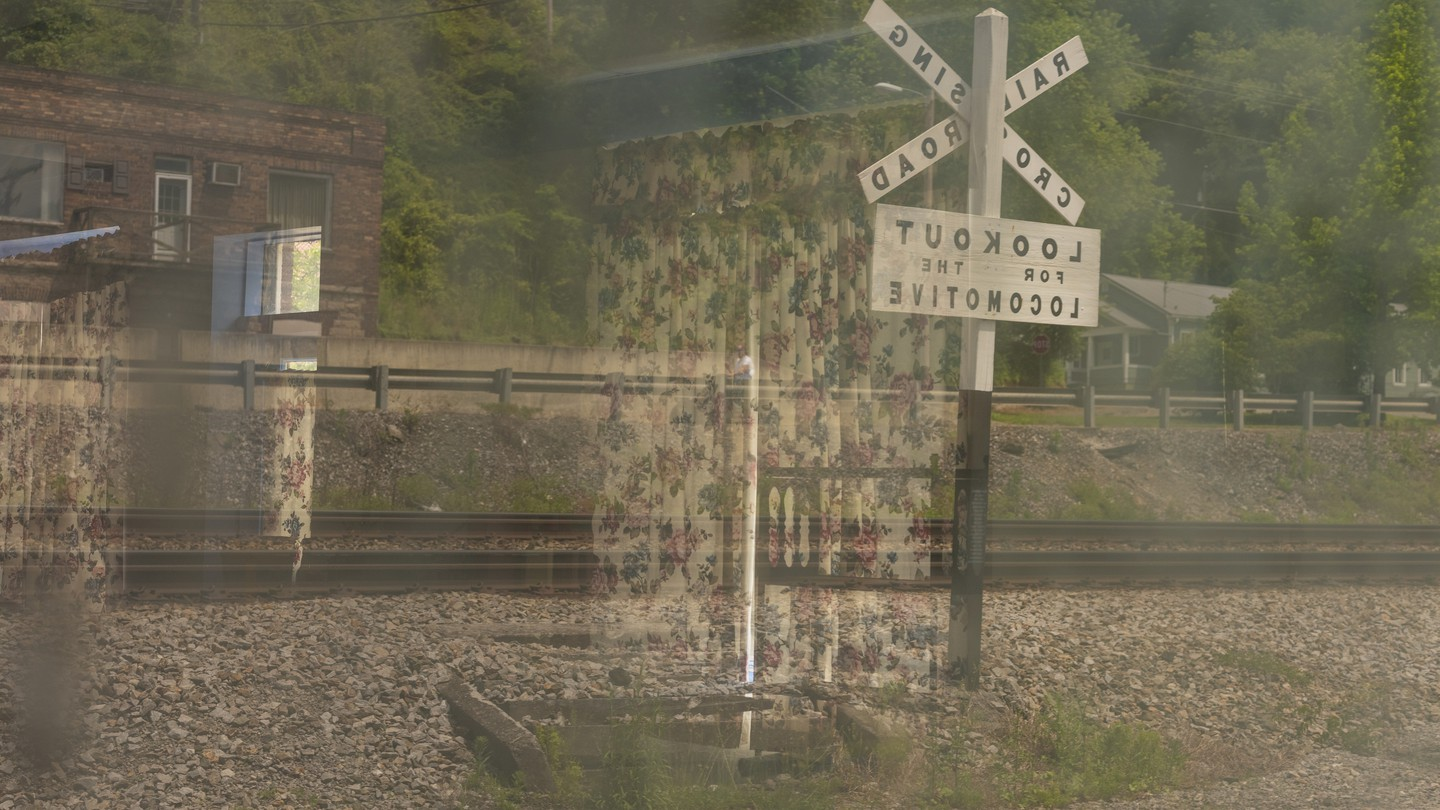 a double exposure of floral curtains on a railroad sign and building