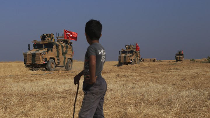 """Turkish armored vehicles conduct a joint ground patrol with American forces in the """"safe zone"""" on the Syrian side of the border with Turkey"""