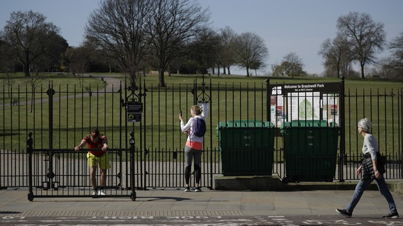 A woman removes her phone and stares through the closed gates of Brockwell Park.