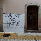 "Graffiti on a wall reads ""Tourist Go Home."""