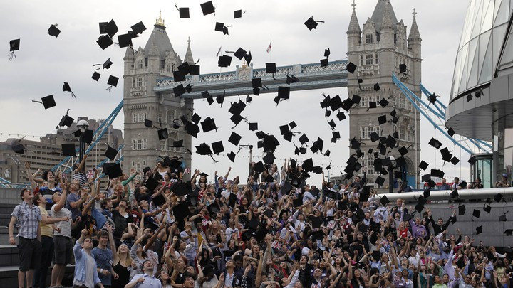 Students toss graduation caps in the air in front of London's Tower Bridge.
