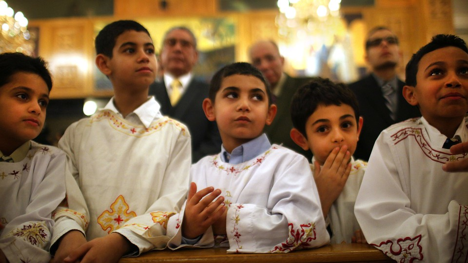 Five boys lean on a wooden pew at a Coptic Orthodox church.