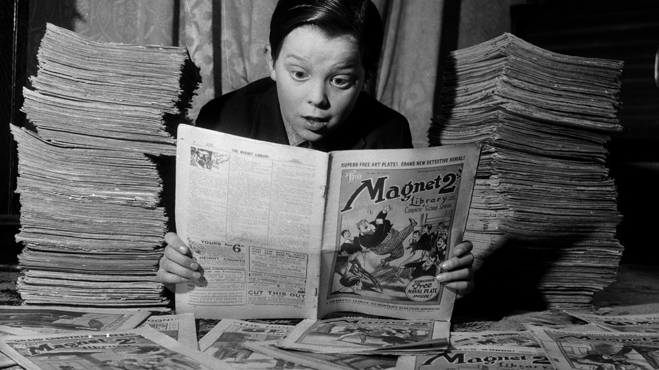 A black-and-white photo of a boy wearing a black shirt and peering at a newspaper comic, with newspapers stacked on both sides