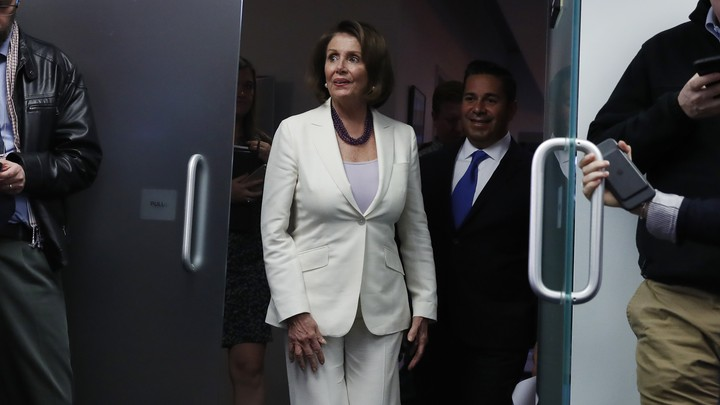 House Minority Leader Nancy Pelosi walks out of a building.