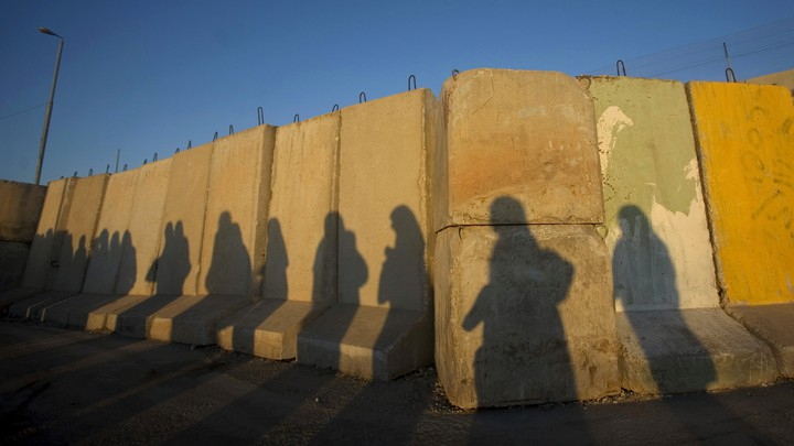 The shadows of Palestinian women at the Qalandiya checkpoint outside the West Bank city of Ramallah
