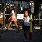 A girl stands with her arm around a parking meter in Los Angeles.
