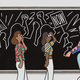 """An illustration of a teacher sitting on a stool, drawing pictures of a civil-rights protest on the chalkboard, while students look on. The protesters' signs say """"Education and Justice"""" and """"NOW."""""""