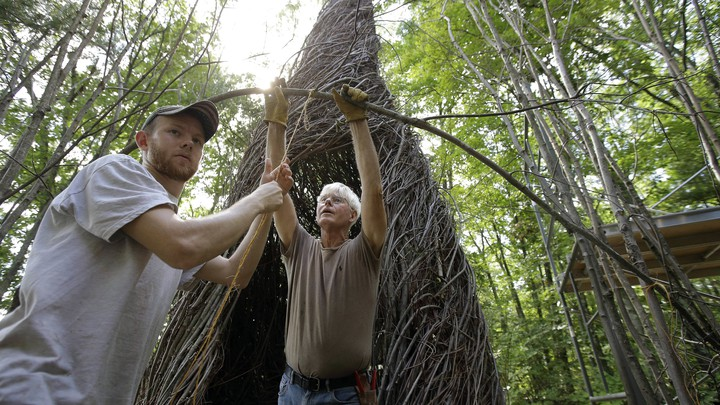 Patrick Dougherty and his son work on a sculpture