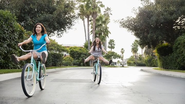 A mother and teen daughter ride bikes.