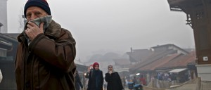 A man shields his face in smog.