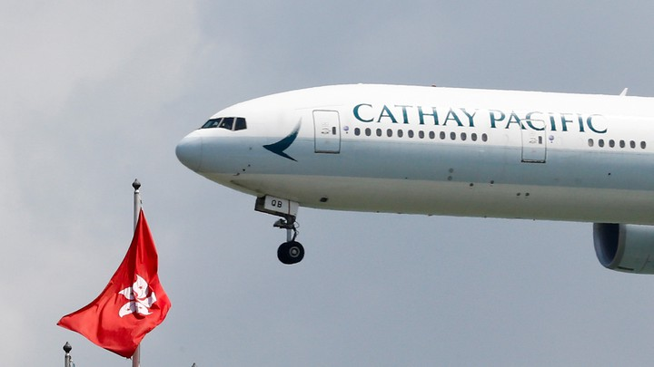 A Cathay Pacific plane hovers beside the flag of Hong Kong.