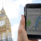 A photo illustration shows the Uber app on a mobile telephone, as it is held up in front of London's Parliament building.
