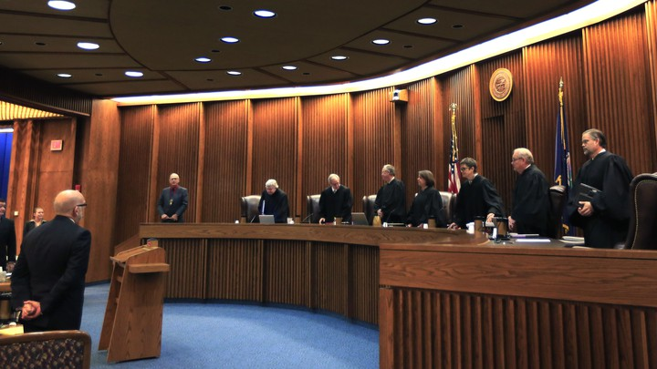 Justices in robes stand in a courtroom.