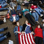 """Eleanor Nuechterlein, 16, hold hands with her mother as they participate in a """"die-in"""" during a protest in favor of gun control reform in front of the White House, Monday, Feb. 19, 2018."""