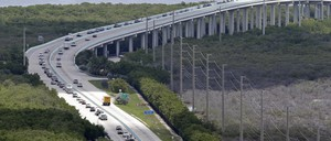 Cars slowed to a standstill on an elevated highway above trees and water with power lines running parallel
