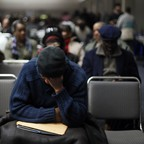 Homeowners facing foreclosure over tax debts wait in a conference room for their cases to be heard in Detroit in January 2015.