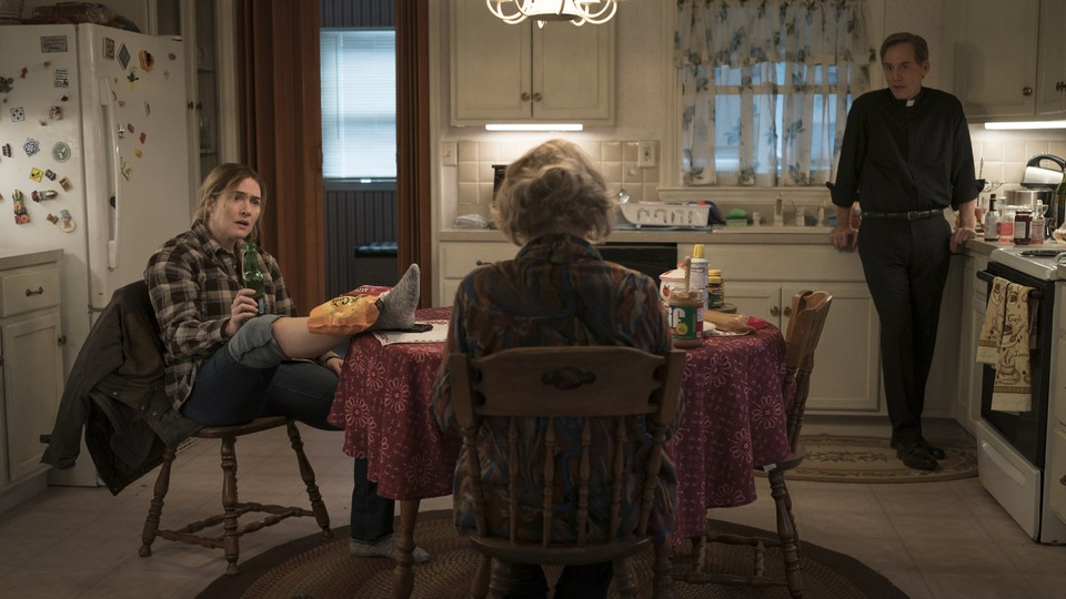 """Characters from the HBO show """"Mare of Easttown"""" gathered around a kitchen table"""