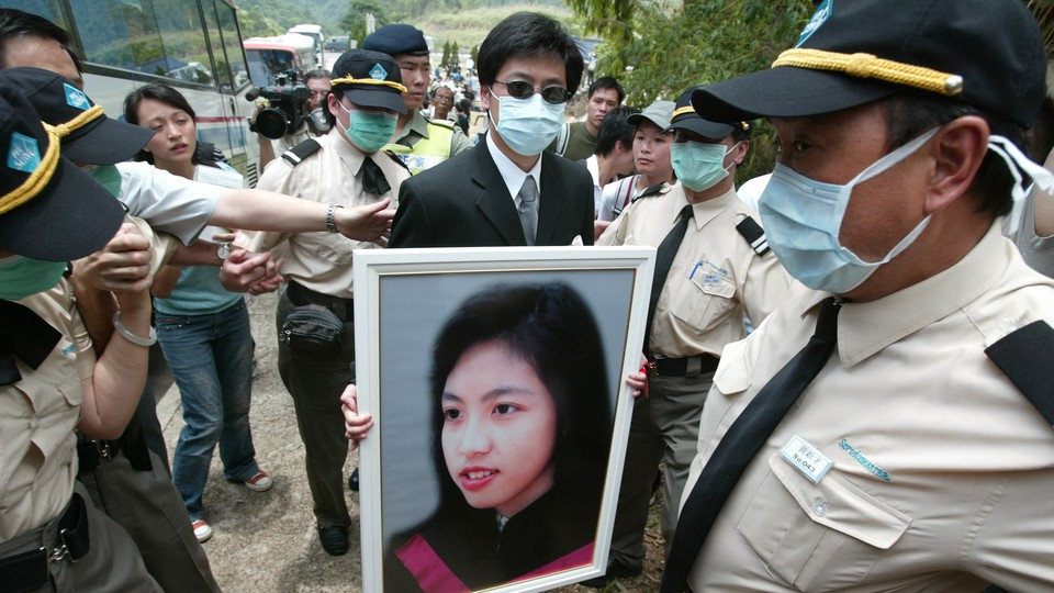 The burial of Dr Joanna Tse Yuen-Man, who died of SARS, at Gallant Garden, Wo Hop Shek. A relative is holding her portrait.