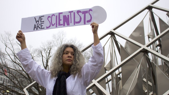 "Dr. Yamilé Molina holds a sign saying 'We Are Scientists' during the Women's March on Washington on Saturday, January 21, 2017. She stands next to the ""Solar Delta"" outdoor sculpture at the National Air and Space Museum."