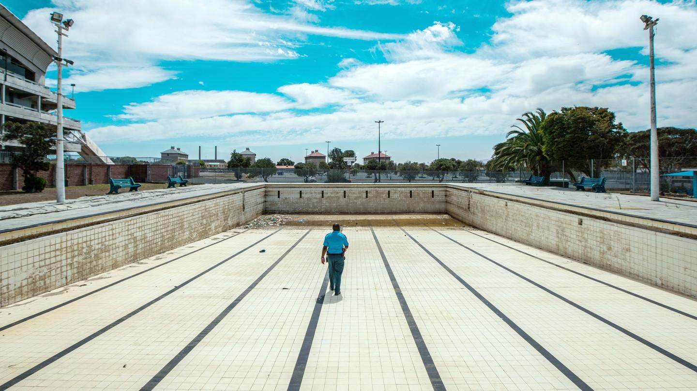 A man walks along the bottom of an empty public swimming pool near Cape Town.