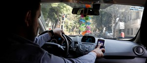 A man checks a route on his phone while in a car.
