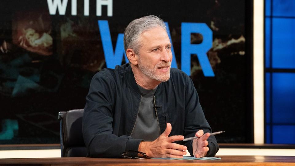 Jon Stewart leaning against a desk, holding a pen