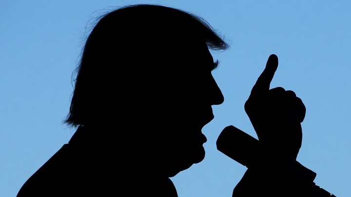 A silhouette of Donald Trump talking into a microphone with his finger pointing to the sky.