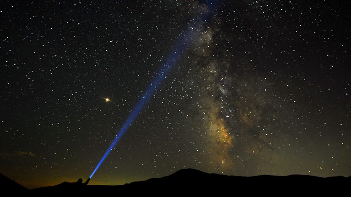 A person shines a flashlight toward the Milky Way in the night sky.
