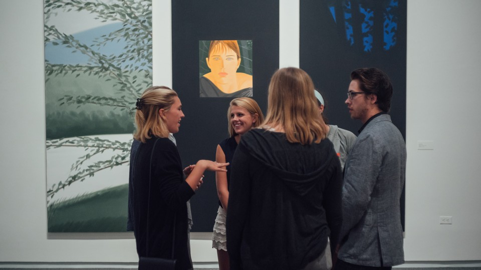 A group of five students stands, chatting, in front of three works of art: two paintings of tree branches and one portrait of a woman's face.