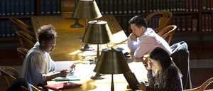 Three people study at a long table in a library hall.