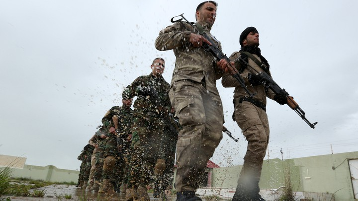 Christians volunteers, who have joined the Kurdish Peshmerga fighters, take part in a training session by coalition forces in a training camp.