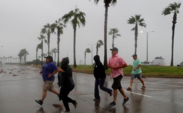 People run across the street during Hurricane Harvey