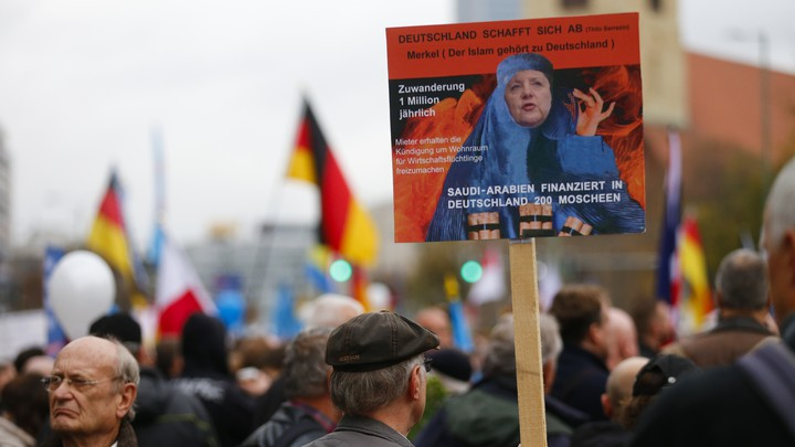 A supporter of the far-right German party AfD holds an anti-Islam, anti-Merkel placard at a 2015 rally.