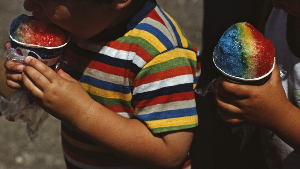 Two children eating snowcones.