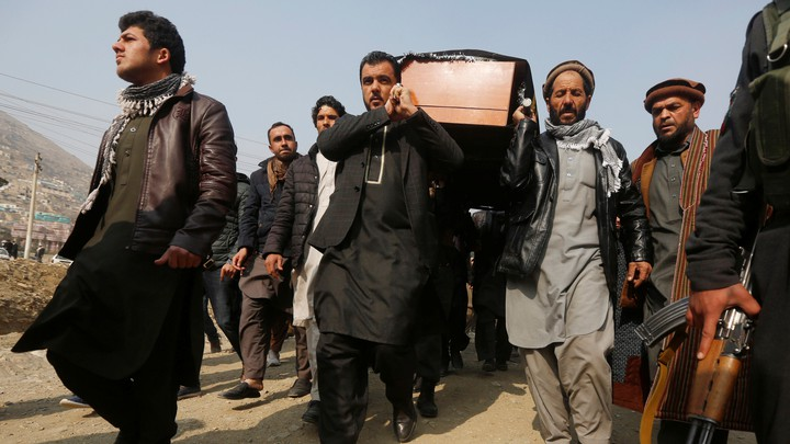 Afghan men carry a coffin.