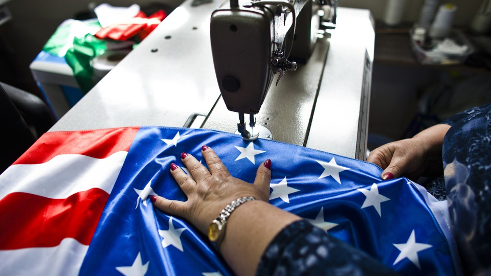 A factory worker sews an American flag