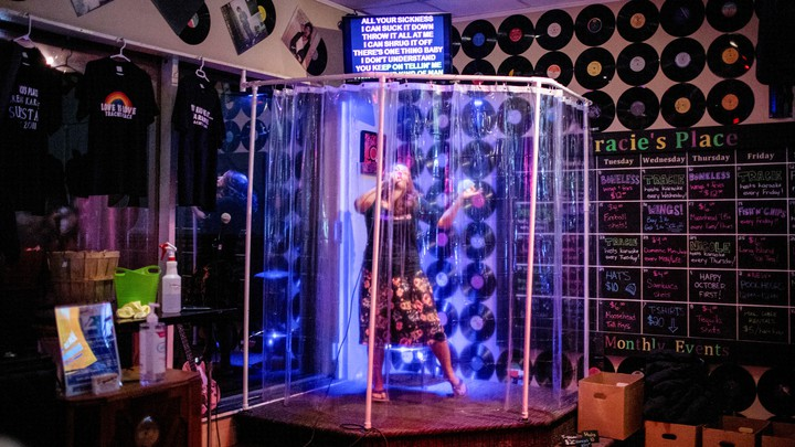 A woman singing inside a shower stall at a karaoke place.