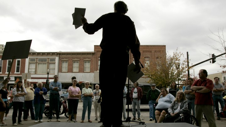 Al Norman, seen in silhouette, holds flyers and speaks to a crowd from a stage.